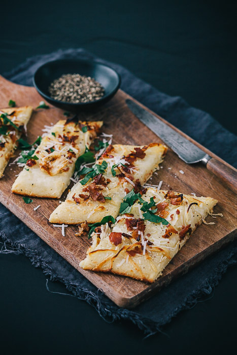 Sliced tarte flambee on a wooden board, on grey material and grey background from an overhead angle.