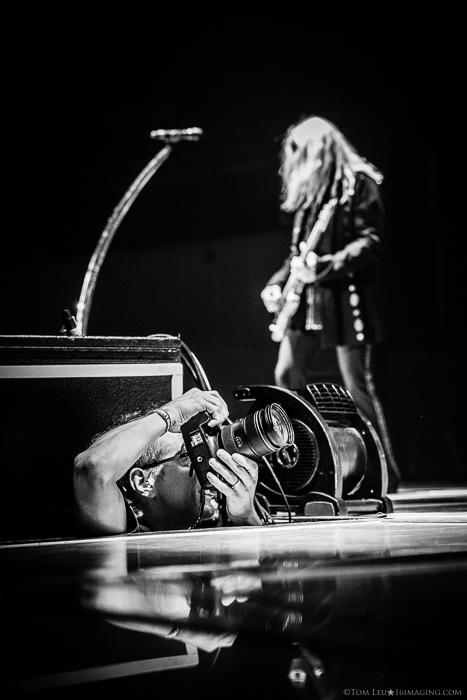 black and white photo of a freelance photographer shooting a concert
