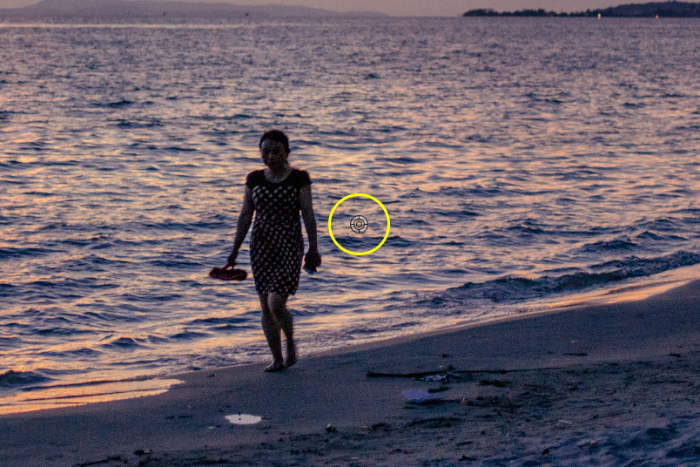 Screenshot showing how to photoshop someone out of a picture using a photo of a woman walking on a beach at evening time