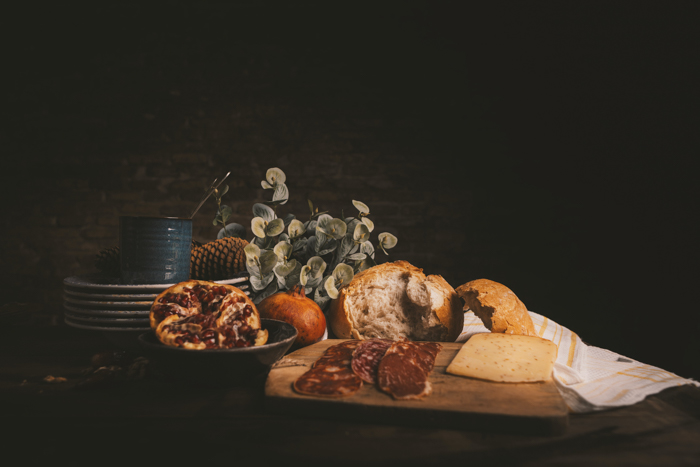 Still life photo with brad, ham, cheese and plates on a table
