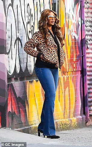 She wore a black blouse underneath a leopard print jacket with blue jeans