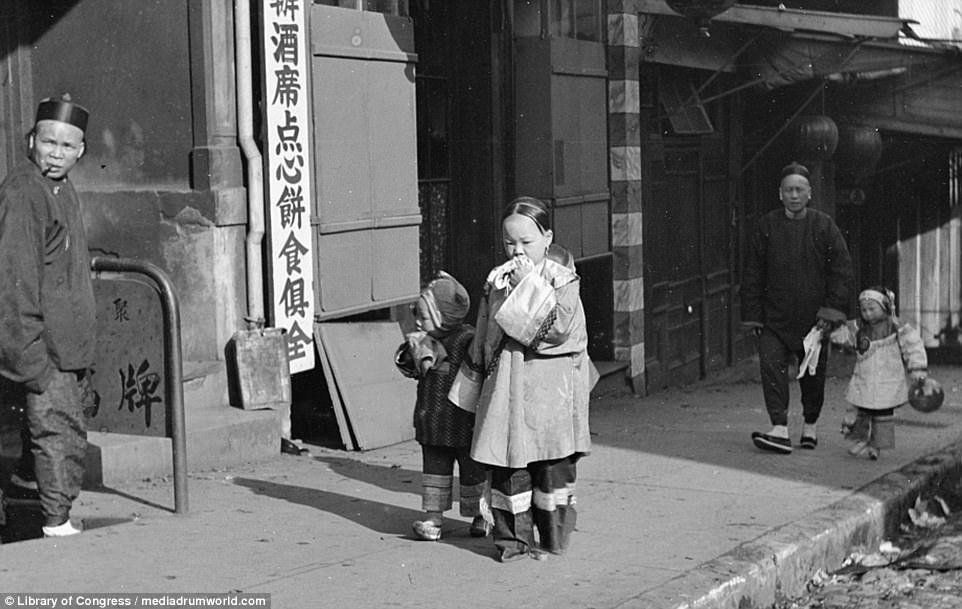 The earthquake hit on April 18 in 1906, with a magnitude of 7.8, and rocked San Francisco and brought Chinatown down. Pictured are children returning to their home before it struck