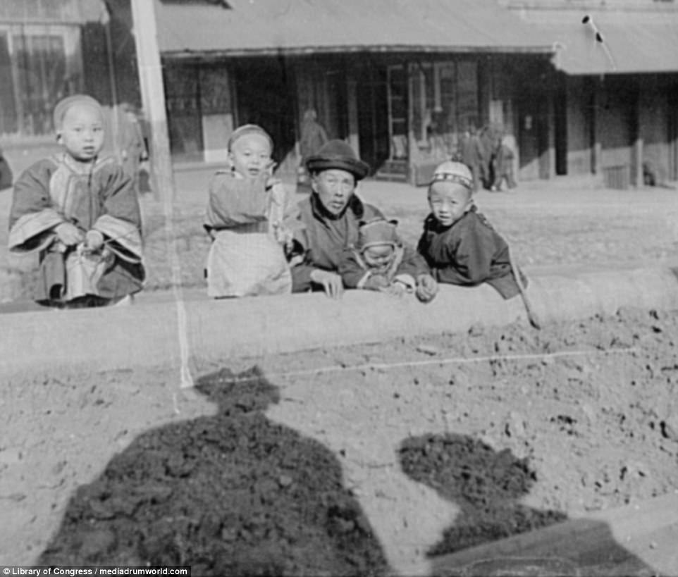 Intrigued: These young Chinatown children seem mesmerised by the photographer